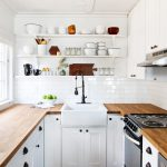 white tiny kitchen remodel with wooden kichen cabinets and countertops plus stoves and sink combined with wall mounted  leaves