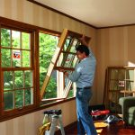 window replacement instalation of awning windows with clear glazing and wooden frame for living room with wooden laminating floor