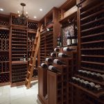 wonderful large wine cellar design in exclusive style with wooden wine racks and straight ladder aside table upon white tile flooring beneath white ceiiling