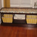 wood bench with three baskets as the storage in the corner of entrance door wood planks flooor