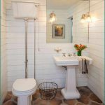 Artistic flooring idea for bathroom single free standing sink and faucet in white plus frameless decorative mirror plus a pair of classic vanity lightings wood planks wall system in white paint color