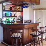 Corner mini wine bar in a home with three wood barstools plus their decorative pillows a lot of wine bottles and wine glasses