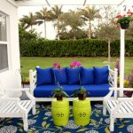 Key West porch style with cozy white chairs and blue sofa two hanging pot and plants florral carpet for porch two unique green table with pots
