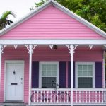 Key West style home design in pink and white tone colors with porch and vertical crafted wood railings