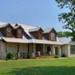 Texas Hill Country home idea with metal roof system white bricks wall system and porch
