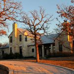 Texas Hill Country residential house style with two chimneys systems and large car port