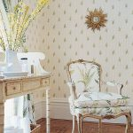 a classic style chair with gold color scheme legs and armrest higher legs console table with drawers in classic design a rattan basket as the storage box floral motif wallpaper