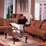 a living room with classic theme brown sofas with classic style craftsmen a classic wood coffee table a classic motif rug wood flooring a brown settee furniture with pillows
