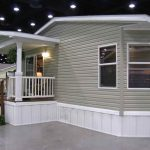 a modern mobile house with natural wood tone rails for stairs and white paint wood rails for front porch