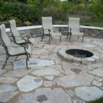 a patio with four series of outdoor furniture in ground round fire pit and Fond du lac stones floors
