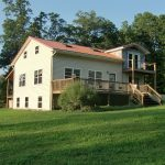 a ranch country home style with larger porch plus vertical wood rail systems and outdoor stairs