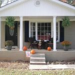 a ranch home style with simple front porch without railing system a pair of darker rattan chairs a pair of beautiful decorative plants on black pots a pair of hanging plants