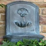 adorable carved concrete gray statue with waterfall above greenery before redish brick wall