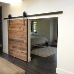 adorable master suit bedroom design with wooden barn door design with black metal rod sliding on black wooden flooring iea with wooden storage and cream sofa