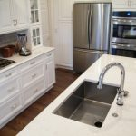 adorable small kitchen design with white wooden cabinetry and cooktop with brick backsplash with small island idea with curved faucet and stainless steel kitchen set