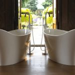 adorable twin victoria and albert tub in white tone and elegant curve style with modern faucet upon bamboo flooring idea with glass window