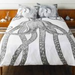 adorable white giant squid fun bed sheets design with unique pattern of squid on the pillows and quilt with floating wooden side table