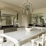 adorable white kitchen design with white cabinetry and classic chandelier above white dining set with black countertop of marble