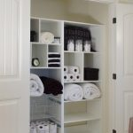 adorable white linen closet organizer design with various small and big slots with rolled towels and white wooden door