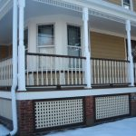Adorable White Porch Design With Vertical Stripe Fence With Poles With Wooden Wall With Glass Accent And Lattice Porch Skirting