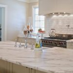 adorable white washed kitchen design with large glass window and modern smokestack and large kitchen island with white patterned marble countertop design