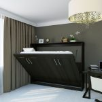 Amazing Black Fold Up Wall Bed Design Idea With Closet Look Beneath Gray Wall Aside Glass Window With Gray Curtain And Desk Upon White Floor Beneath Large Chandelier
