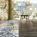 amazing hanging out spot with wooden reclining chair and table and wooden floor and blue patterned casa antica tile with stone wall