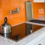 amazing orange colored acryic backsplash idea withhanger and modern white cabinetry with gray marble countertop with induction stove