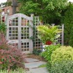 arched gate white lattice fence design beneath shady tree design with shrub with purple plant with concrete patio