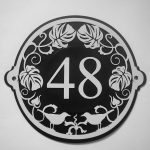artistic art deco house numbers plate with beautiful ornament with white wall paint