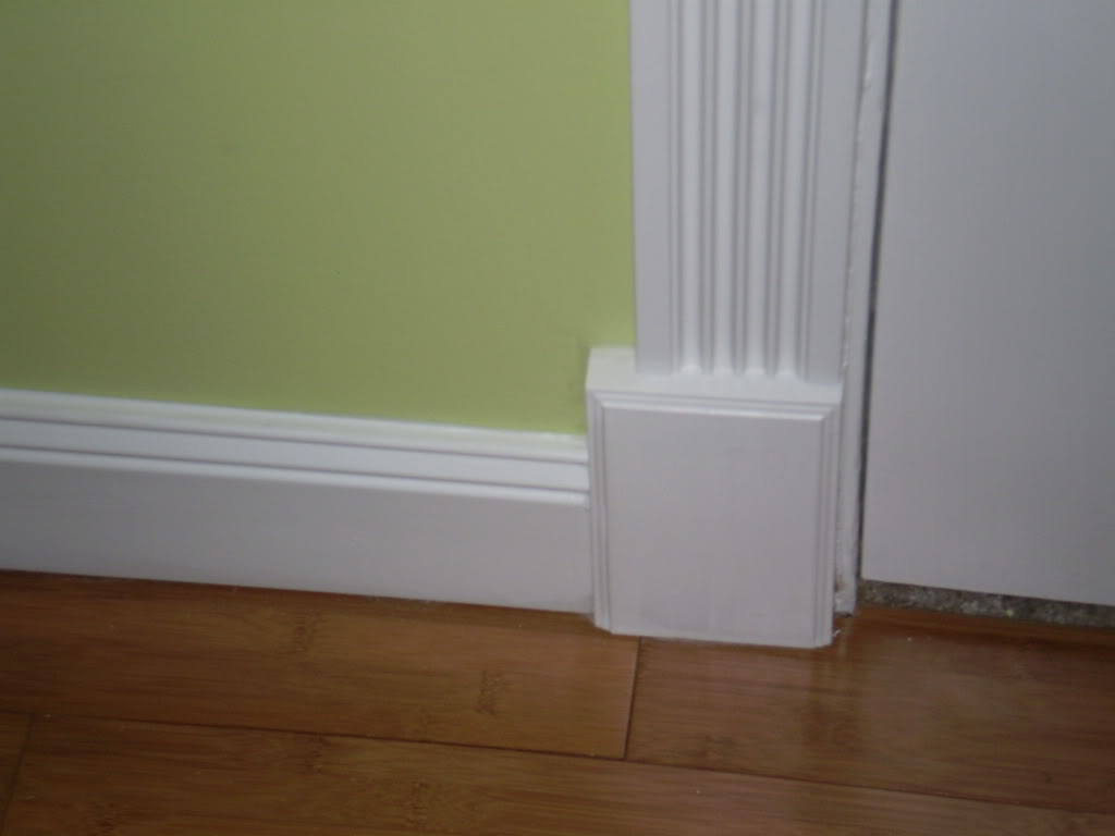 Baseboard Trim Styles In White Combined With Green Painted Wall And Hardwood Flooring