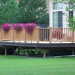 beautiful large and long porch idea made of wood with wooden vertical fence with black porch skirting idea and purple flower decoration with grassy meadow