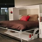 bed that folds into wall with shelving plus wooden cabinets and tile floor plus brown bedding set