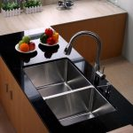 best kitchen sink material with double stainless steel sink and faucet plus black countertops on wooden kitchen cabinets