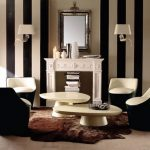black and white vertical stripes tone colors for wall a pair of wall lighting in white a fireplace mantel used as book storage a classic metal framed mirror chairs in black outside and white inside