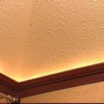 brown wooden flat crown molding design beneath textured white concrete ceiling design with metal rod