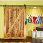 cheerful sliding wooden barn doors for closets in traditional style combined with hanging jackets and bag plus wooden storage and hardwood flooring with mats