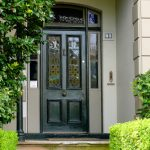 classic  black screen door with mosaic screen and sidelights