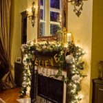 classy christmas decorations for mantels fireplace with green garland and string lights plus scented candles and framed mirror with wall candle holders