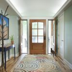 colorful entry way rugs with glass and wood door with wooden side table and painting on wall decoration plus wooden floor
