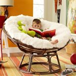 comfortable chairs for reading with egg shapes and soft rug and wooden legs and frames plus cute doll for kids