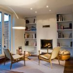 comfy chairs for small spaces with glass door and curved lighting  and bookshelf plus modern fireplace and rug