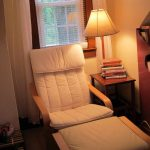 comfy reading chair for bedroom with square end table with table lamps on top plus books and windows with blinds and curtains plus book shelf