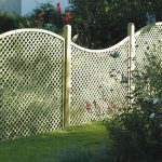 curved modern white lattice fence design with pole upon grassy meadow beneath shady tree with decortaive plant