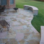 curved stone outdoor flooring over concrete desin with concrete bench and metal seating aside reddish brick house