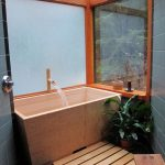 deep tubs for small bathrooms with japanese style and glass windows and black tile floor plus plant pot for natural look