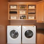 Double Machines Of  Washer And Dryer Beneath Natural Wooden Cabinet In Cream Laundry Room With Cream Tile Flooring Design