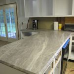 dull white kitchen cabinetry with white washed soapstone countertop with white upper cabinet with glass window