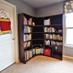 eclectic black wooden corner bookshelf deign beneath gray wall aside white wooden door and glass window upon cream floor