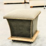 elegant black cream ottoman storage design with wheels and wooden accent and table cloth patterned bolster
